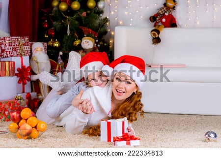Portrait of happy mother and adorable daughter in suit of Santa's little helper near the christmas tree - stock photo
