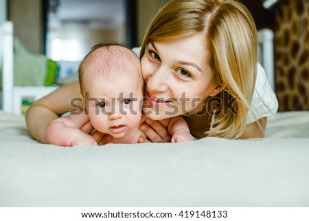 Portrait of happy mother and baby at home. The child is 2 months - stock photo