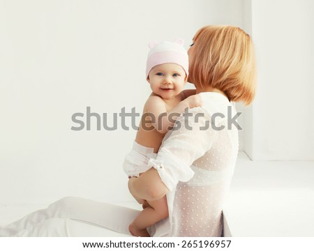 Portrait of happy mother and baby at home together in white room near window - stock photo