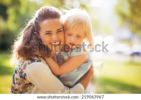 Portrait of happy mother and baby girl hugging - stock photo