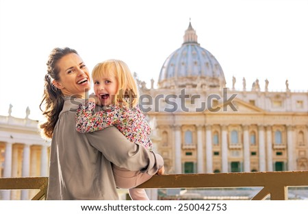 Portrait of happy mother and baby girl in front of basilica di san pietro in vatican city state - stock photo