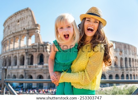 Portrait of happy mother and baby girl in front of colosseum in rome, italy - stock photo