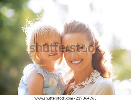 Portrait of happy mother and baby girl outdoors in park - stock photo