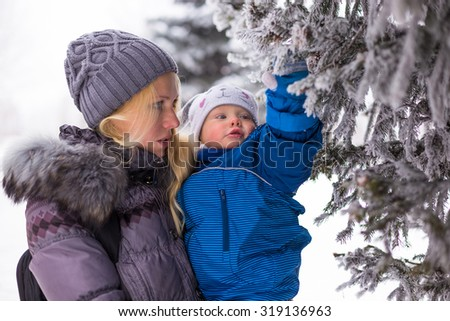 Portrait of happy mother and baby near evergreen spruce in winter park  - stock photo