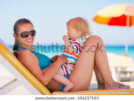 Portrait of happy mother and baby on sun bed - stock photo