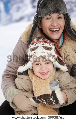 Portrait of happy mother and child holding cup of hot tea in snow on a cold winter day laughing, smiling. - stock photo