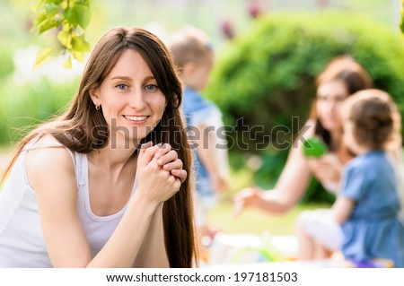 Portrait of happy mother and child with her friends on background - stock photo
