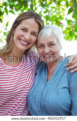 Portrait of happy mother and daughter with arm around while standing outdoors - stock photo