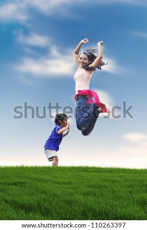 Portrait of happy mother and her daughter jumping on the meadow. shot outdoor during summer - stock photo