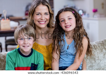Portrait of happy mother and kids sitting on a sofa at home - stock photo