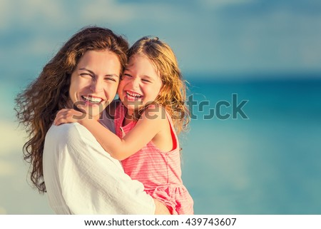 Portrait of happy mother and little daughter on sunny beach - stock photo