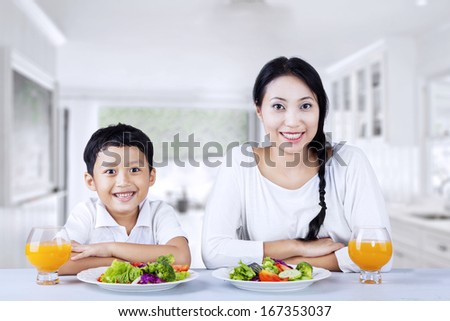 Portrait of happy mother and son having salad in the kitchen - stock photo