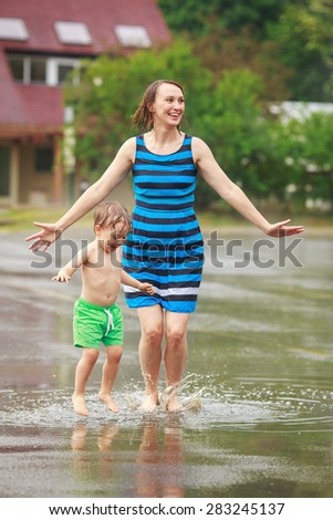Portrait of happy mother and son jumping in puddles during the rain thunderstorm on a bright summer day outside, sports recreation leisure concept, family activity - stock photo