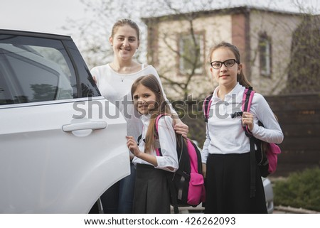 Portrait of happy mother and two girls with school bags posing at the car - stock photo