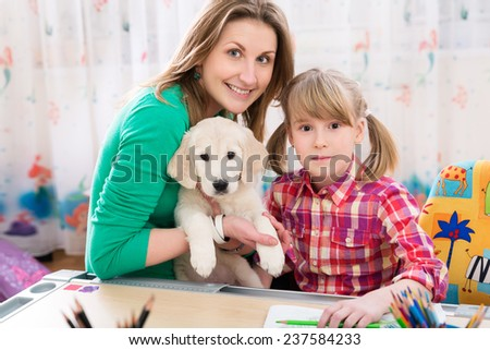 Portrait of happy mother, daughter and puppy at home - stock photo