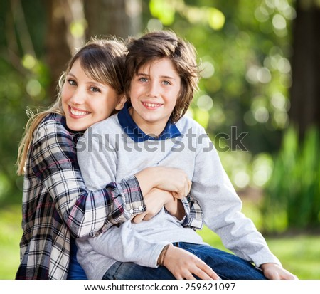 Portrait of happy mother embracing son at campsite - stock photo