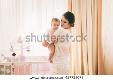 Portrait of happy mother holding her baby at bedroom - stock photo