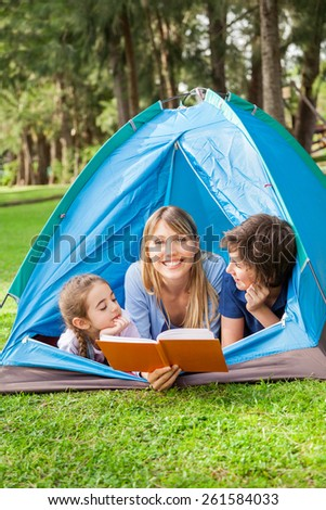 Portrait of happy mother reading book for children at campsite - stock photo