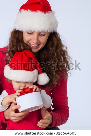 Portrait of happy mother with cute baby in Christmas hat - stock photo