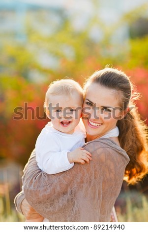 Portrait of happy mother with smiling baby on street - stock photo