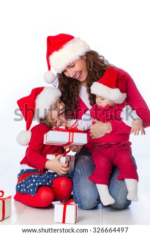 Portrait of happy mother with two cute daughter in Christmas hat - stock photo
