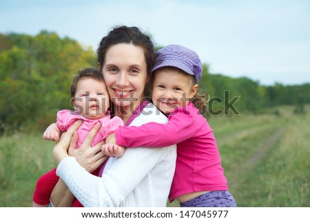 portrait of happy mother with two cute little daughters outdoors - stock photo