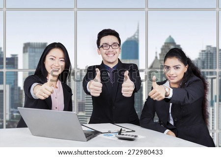 Portrait of happy multi ethnic businesspeople showing thumbs up in a meeting at the office - stock photo