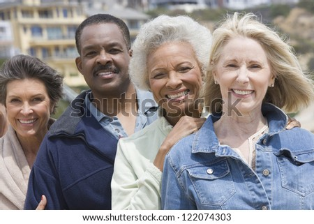 Portrait of happy multi ethnic friends standing together - stock photo