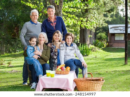 Portrait of happy multi generation family enjoying picnic in park - stock photo