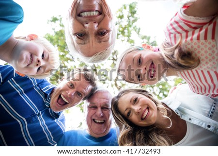 Portrait of happy multi-generation family forming a huddle in park on a sunny day - stock photo