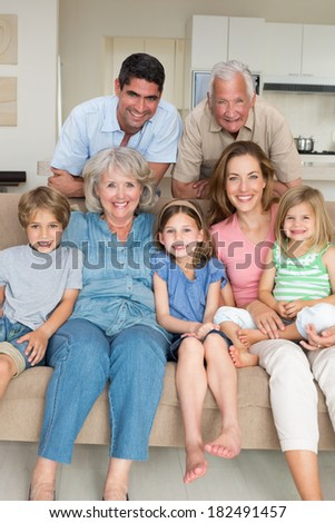 Portrait of happy multigeneration family in sitting room at home - stock photo