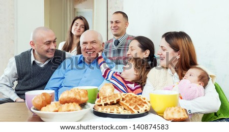 Portrait of happy multigeneration family or group of friends posing together over tea - stock photo