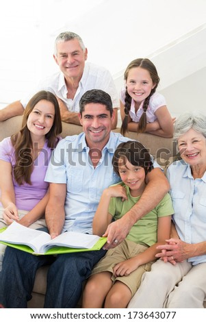 Portrait of happy multigeneration family with book at home - stock photo