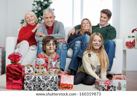 Portrait of happy multigeneration family with Christmas gifts sitting in house - stock photo