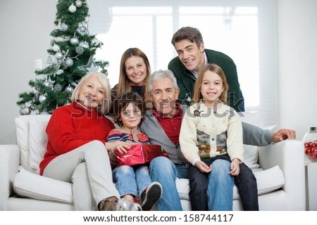 Portrait of happy multigeneration family with Christmas present in house - stock photo