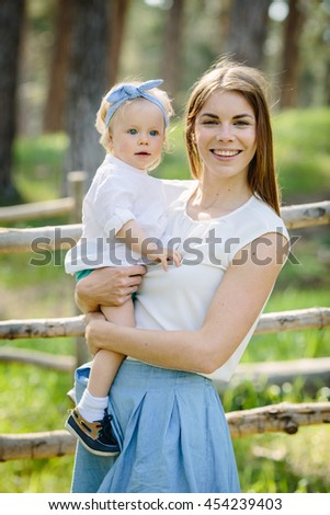 Portrait of happy mum and her little baby daughter outdoor in the park - stock photo