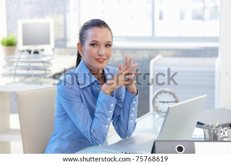 Portrait of happy office worker girl sitting at desk, smiling, looking at camera. - stock photo