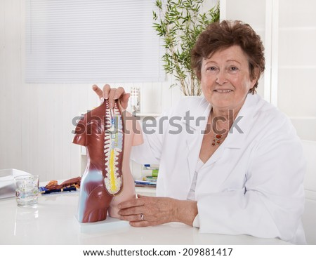Portrait of happy older senior doctor explaining the human body with a torso. - stock photo