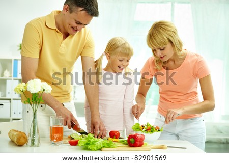 Portrait of happy parents and their daughter cooking salad in the kitchen - stock photo