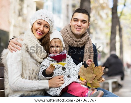 portrait of happy parents with children in autumn. Focus on woman's eyes - stock photo