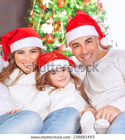 Portrait of happy parents with cute little daughter wearing red Santa hat sitting near beautiful Christmas tree and celebrating religious holiday - stock photo