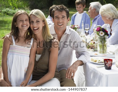 Portrait of happy parents with daughter at dining table with family in background - stock photo