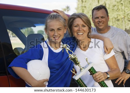 Portrait of happy parents with daughter holding soccer trophy - stock photo