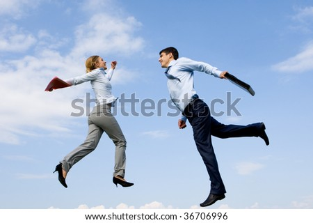 Portrait of happy partners jumping against blue sky - stock photo