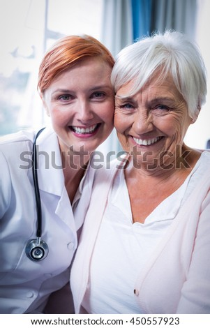 Portrait of happy patient and doctor at home - stock photo