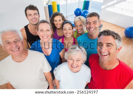 Portrait of happy people standing together at gym - stock photo