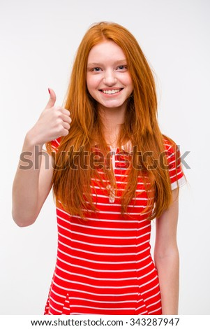 Portrait of happy positive smiling attractive young redhead woman in red striped dress with thumbs up gesture over white background - stock photo