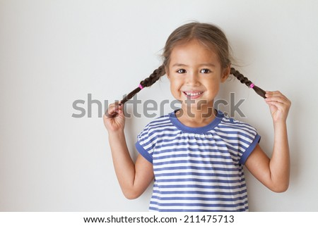 portrait of happy, positive, smiling, playful asian caucasian girl, playing with her braid - stock photo
