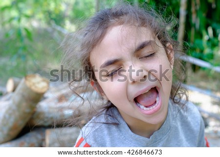 portrait of happy, positive, smiling, playful mixed race asian caucasian girl, candid of smiling girl playing in countryside park home, little childhood mixed race girl - stock photo