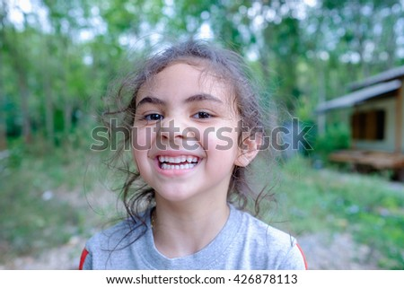 portrait of happy, positive, smiling, playful mixed race asian caucasian girl, candid of smiling girl playing in countryside home, little childhood mixed race girl - stock photo